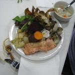 salmon, vegetables, soup and other traditional foods on a plate