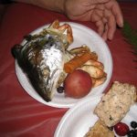 fish head, vegetables, and potatoes on a plate